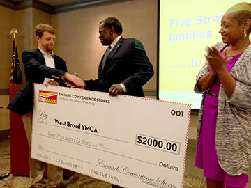 Matt Clements, Director of Marketing for Enmark Stations presents Norm Joyner, Interim Executive Director and Chiquita Hanna, Operations Director of the West Broad Street YMCA a check for $2000 raised through the Enmark Encourage Health Education Series 2014.
