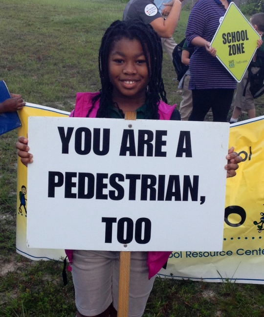 Lexus Axon, a 3rd Grader from Windsor Forest Elementary School, holds a sign to cars on Windsor Rd.