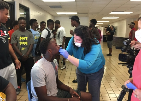 Sophomore Quarterback Earl Hamilton, of Groves High School Football team receives a mouth shield guard from Dr. Angela Canfield