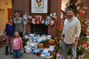 mason-howington-dr-corinne-howington-and-meg-howington-kneeling-drop-off-donated-items-to-bill-sorochak-at-the-ronald-mcdonald-house-of-the-coastal-empire